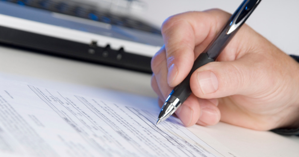 man holding a pen writing a signature, computer in background